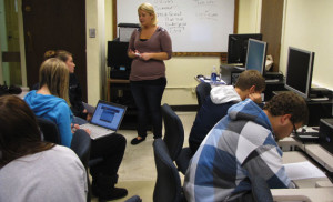 Instructor Randi Anderson teaches students in a basic writing class in Scobey Hall. As a lecturer, she gains the necessary experience in teaching that she will need in order to obtain more full-time/tenured positions. She notes that instructors are offered opportunities to become more familiar with and trained in important instructional resources.
