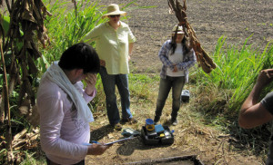 Jackson, center, looks on as Federal University of Western Para students open an archaeological unit at the edge of a rain forest near a plowed cornfield comprised of terra preta soils.