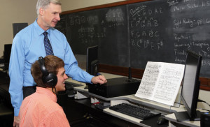Professor John Walker watches Brian Wynia, a senior music minor from Sioux Falls, perform in the new keyboard lab in Lincoln Music Hall Dec. 13, 2012. The notes he plays off the sheet music in front of him are heard on the headphones he is wearing and seen on the computer screen to his right.
