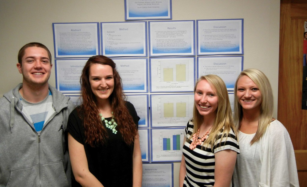 Allyson Lucht, second from left, stands next to her poster presentation from the research methods/statistics course spring 2014. Pictured from left are Alex Fodness, Lucht, Amber Wodzinski and Miranda Wagner.