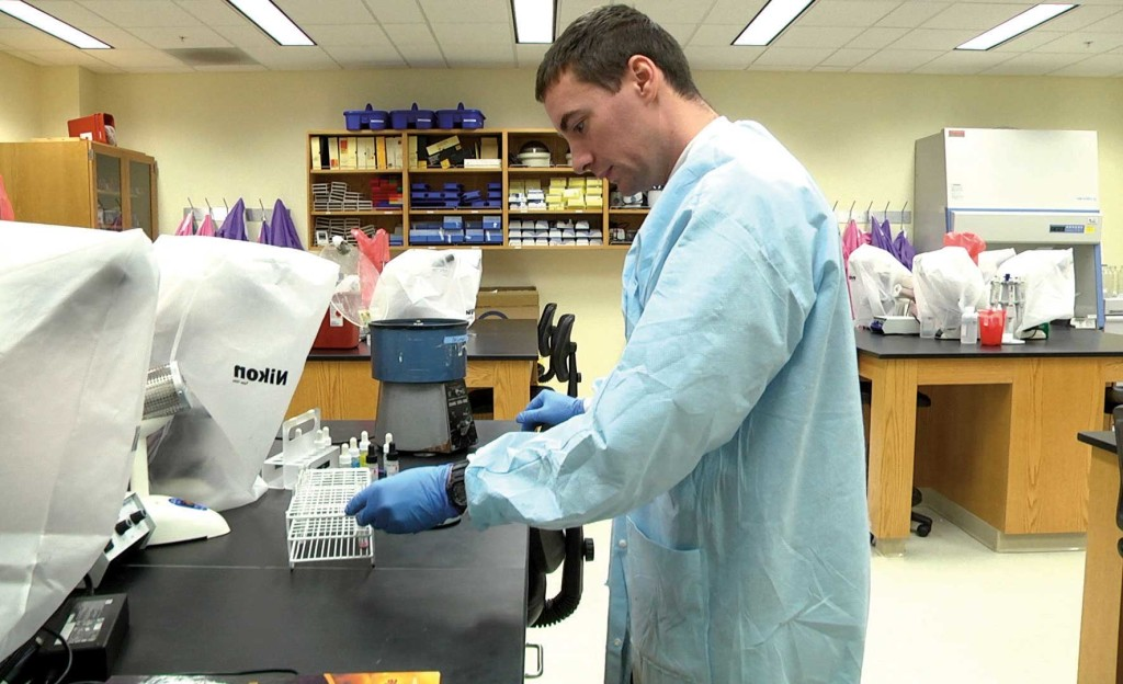 Richards works with blood samples in a laboratory in the Avera Health and Science Center.