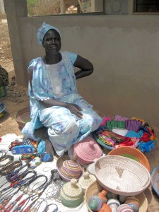 A Sengalese woman shows traditional handwoven baskets, which are made in many colors and designs.