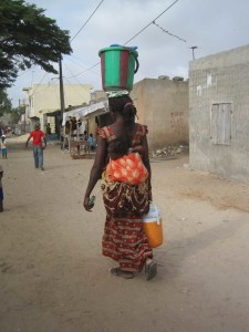 A Sengalese woman carries water and her baby